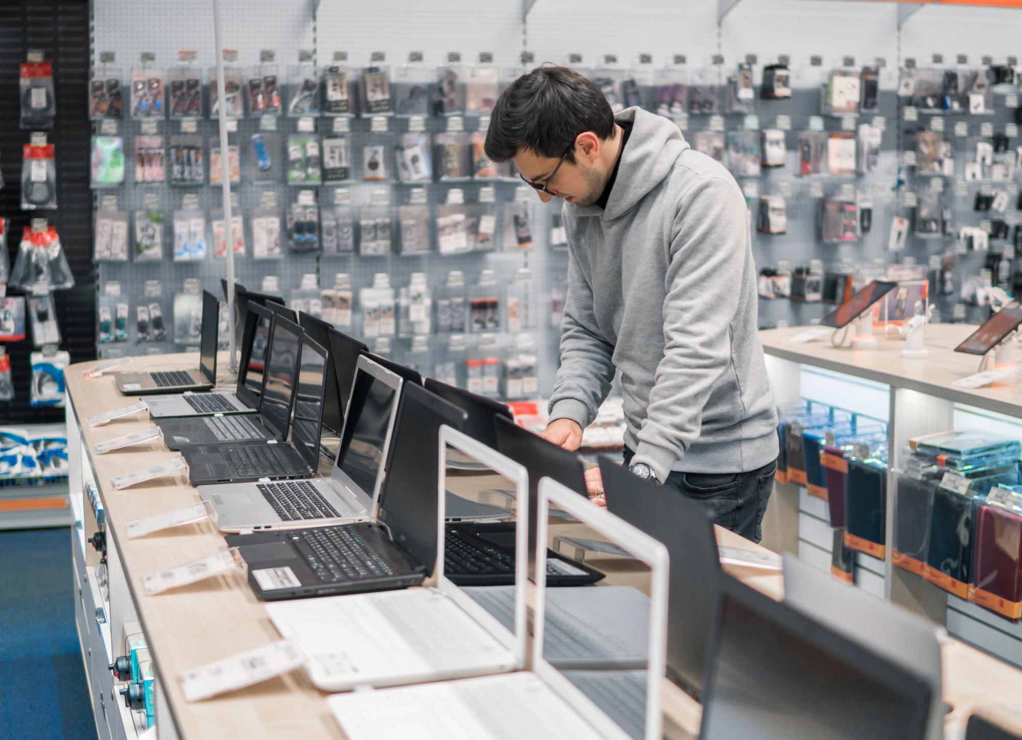 modern male customer choosing laptop in the computer store